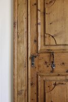 Restored, rustic panelled door with traditional, wrought iron handle