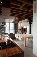 Kitchen counter with rustic wooden worksurface and extractor hood; modern dining area below paper pendant lamp