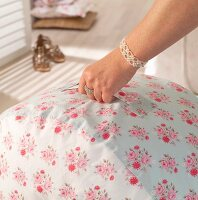 Pouffe with handle and hand-sewn, floral cover held by woman's hand with jewellery