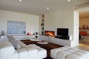 Interior with white designer sofa and set of coffee tables in front of fireplace in wall with shelf niches and masonry shelf running around two walls