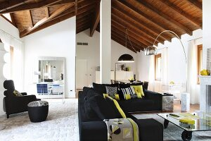 Black sofa set and cushions with lime green accents around coffee table on castors in open-plan interior with exposed, wood-beamed ceiling