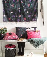 Cushions with hand-sewn covers in ethnic, hippy style on wooden bench below wall hanging