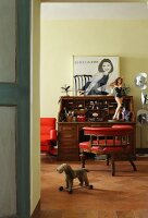 Antique armchair with light red upholstery, bureau decorated with pin-up figurine and vintage advertising sign and toy dog on wheels