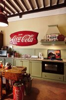 Wooden kitchen in pale vintage green with retro advertising signs, Coca-Cola barrels and old workbench used as counter