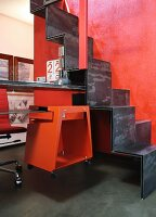 Metal samba staircase with integrated desk, stool on castors hung on shelf and red back wall