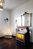 Retro jukebox under gilt-framed, antique mirror, modern artwork and unusual light sculpture in white interior