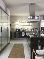 Kitchen with central island counter and fitted cupboards with glossy fronts