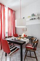 A dining area with old and new chairs against a window with red-and-white stripped curtains in a renovated kitchen
