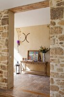 A wide entrance through a natural stone wall with a view of a wall table in a traditional hallway