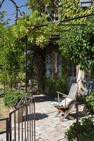 Kleine Steinterrasse mit berankter Eisenpergola vor provenzalischem Gästehaus mit klassisch hellblauen Fensterläden