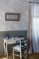 Framed embroidery above small, antique desk with rush-bottomed chair; marbled walls and curtains in natural shades