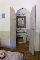 Masonry washstand in ensuite bathroom seen through open double doors; corner of bed with floral bedspread