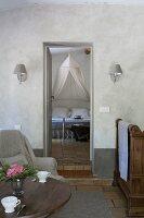 Holztisch mit nostalischen Kaffeetassen, Sessel und Recamiere, Blick durch offene Tür auf Doppelbett mit Moskitonetz