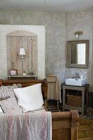 Antikes Bett mit hölzernen Seitenteilen, Wandelement mit Leuchte und Ablage auf Trennmauer zur Toilette, daneben ein schlichter Waschtisch