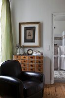 Black leather armchair and ornaments on vintage apothecary's cabinet below picture on wall