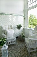 White wicker chairs with pale cushions in conservatory with tiled dado