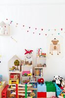 Toys stacked on floor and in cubic shelves on wall below bunting