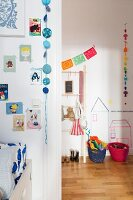 Hand-crafted garlands, comics and pictures stuck to walls with washi tape in child's bedroom; view into cloakroom