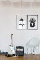Black and white graphic artworks above shell chair, electric guitar andd amplifier