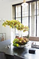 Fruit bowl and vases of flowers on black table in front of window with dark louvre blind