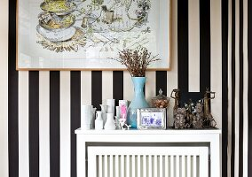 Vases and ethnic artworks on white radiator cover against wallpaper with wide black and white stripes