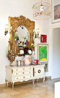 White Rococo-style cabinet below ornate gilt-framed mirror combined with modern artworks and photos in hallway