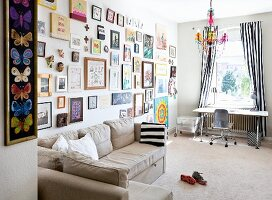 Beige corner sofa below large gallery of pictures on wall; desk below window with floor-length, black and white striped curtains