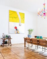 Cane cantilever chairs around dining table below colourful chandelier with multicoloured glass droplets in front of modern painting on wall