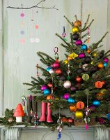 Christmas tree with multicoloured baubles, wellington boots and festive ornaments on mantelpiece