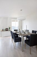 Black-upholstered chairs at set dining table below round pendant lamps with white lampshades in minimalist interior