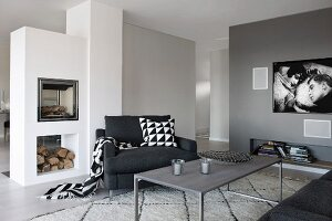 Grey-painted lounge area with delicate coffee table, black armchair and masonry fireplace