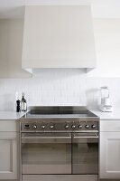Detail of kitchen counter with modern stainless steel cooker with induction hob below white-clad extractor hood