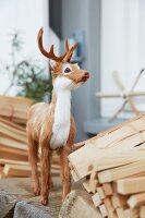 Junger Hirsch als Dekotier zwischen Holzscheiten