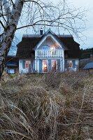 Blick vom Garten auf reetgedecktes Wohnhaus in Abendstimmung