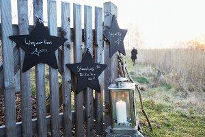 Sternförmige Wegweiser aus schwarz lackiertem Holz an Zaun gehängt, davor Laterne mit Kerze, im Hintergrund Spaziergängerin