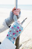 Ast haltende Frauenhände mit gestrickten Pulswärmern