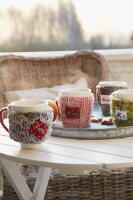 Mugs with knitted covers and name tags on a table outside