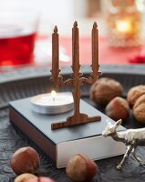 A mini candelabra made from walnut wood with a burning tealight in front of it on a box of matches with nuts as decoration