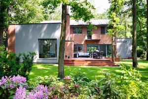 Modern house with brick facade, rendered elements, terrace & summer garden