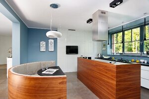 Bench with curved wooden back and free-standing kitchen counter with walnut-clad front in open-plan kitchen