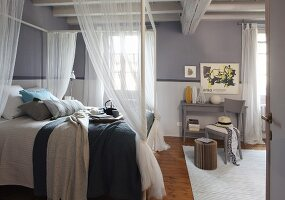 Rustic bedroom with grey-painted walls and four-poster bed with translucent curtains below wood-beamed ceiling