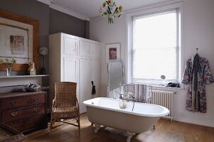 Wicker chair next to free-standing, vintage-style bathtub in cosy bathroom
