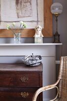 Detail of antique chest of drawers in front of mantelpiece holding vase of flowers and Art Nouveau table lamp