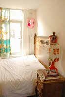 Retro table lamp on antique bedside table next to bed with carved headboard in small bedroom