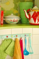 Kitchen utensils hanging from wall hooks under green-painted shelf holding enamel teapot and pan