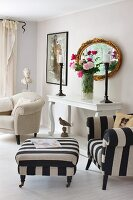 Armchair and footstool with black and white striped upholstery next to bouquet in front of antique, gilt-framed mirror on vintage console table