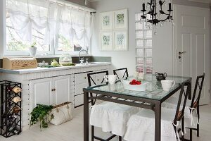 Dining table with glass top and metal frame, chairs with white loose covers and kitchen counter below window with translucent gathered blinds