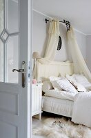 Double bed with translucent canopy and white animal-skin rug in country-house-style bedroom