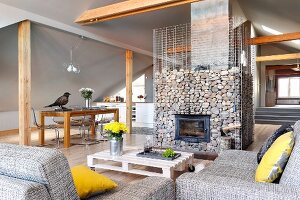 Yellow scatter cushion on grey marl sofa and low coffee table in front of fireplace in gabion cage in converted attic with pale grey walls