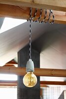 Pendant lamp with simple light bulb and cord wrapped around wooden beam